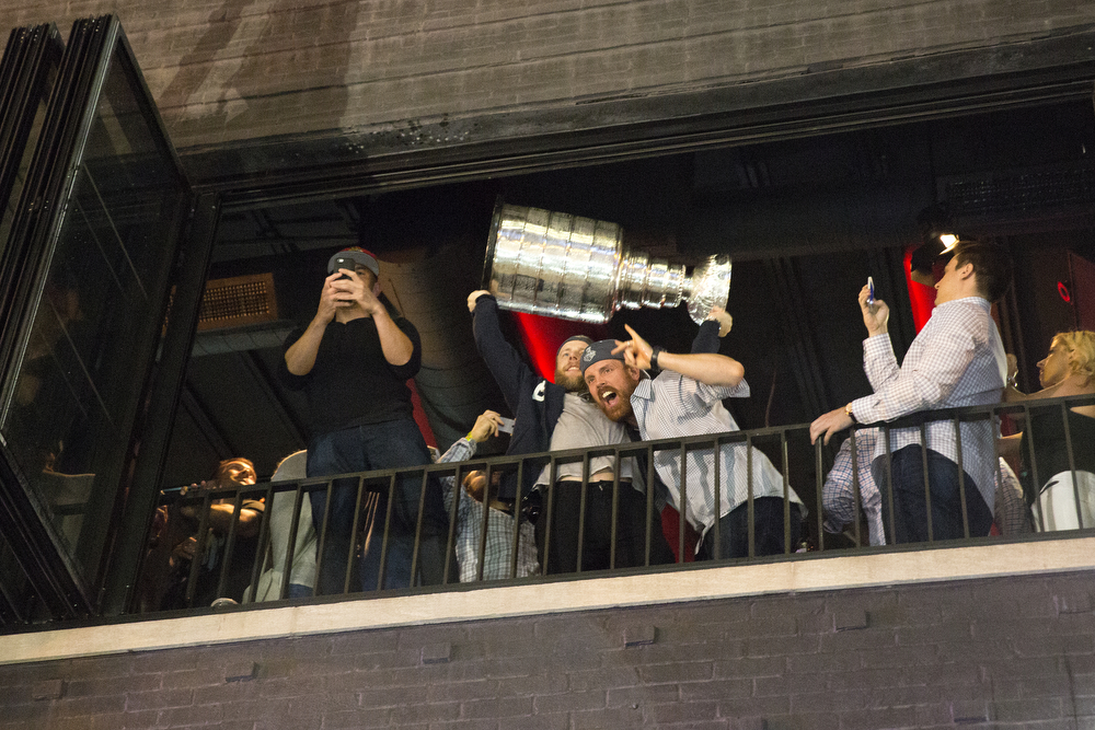 Blackhawks winger Kris Versteeg, left, holds up the Stanley Cup next to center Brad Richards on the balcony of Rockit Bar & Grill in downtown Chicago as they celebrate their win Tuesday, June 16, 2015. (Erin Hooley/Chicago Tribune)