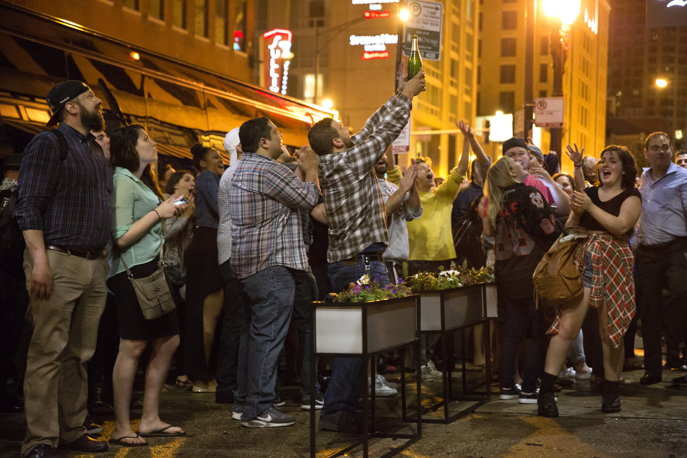 A fan holds up a bottle of champagne that was dropped from the balcony of Rockit Bar & Grill in downtown Chicago as the Blackhawks celebrated their Stanley Cup win inside Tuesday, June 16, 2015. (Erin Hooley/Chicago Tribune)