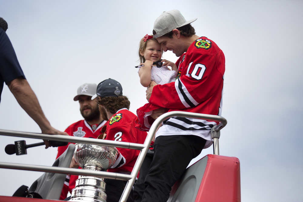 A clean-shaven Patrick Sharp holds his daughter on a bus with the Stanley Cup at the United Center in Chicago for the start of the championship parade on June 18, 2015. (Erin Hooley/Chicago Tribune)