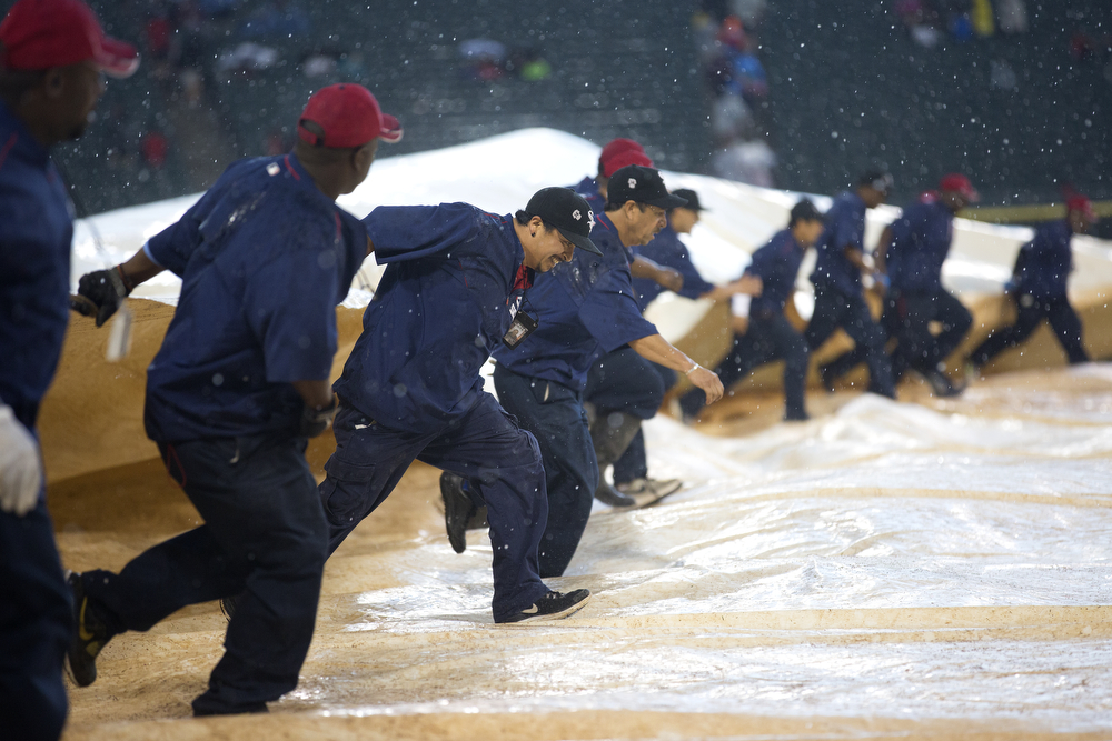Workers roll out the tarp during a downpour that caused a delay of the Chicago White Sox versus Houston Astros game at U.S. Cellular Field in Chicago Monday, June 8, 2015. (Erin Hooley/Chicago Tribune)