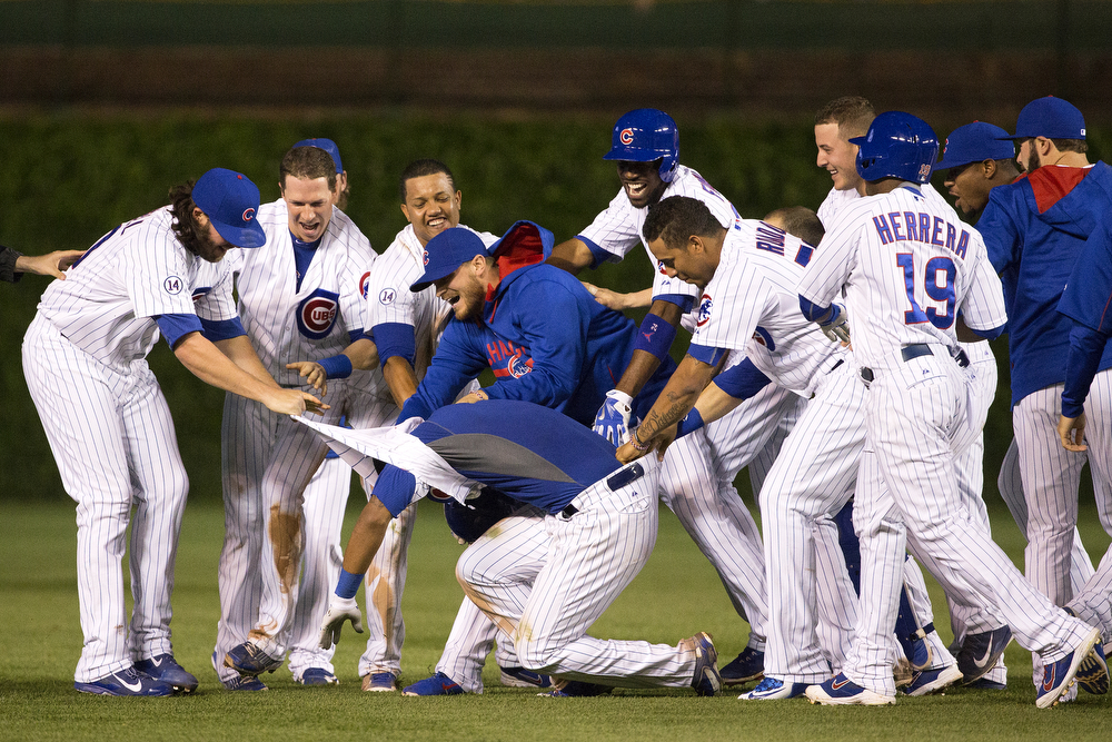 The Chicago Cubs tackle teammate Addison Russell after he made a hit into the outfield, allowing Jonathan Herrera to score and win the game against the Washington Nationals 3-2 at Wrigley Field Tuesday, May 26, 2015. (Erin Hooley/Chicago Tribune)