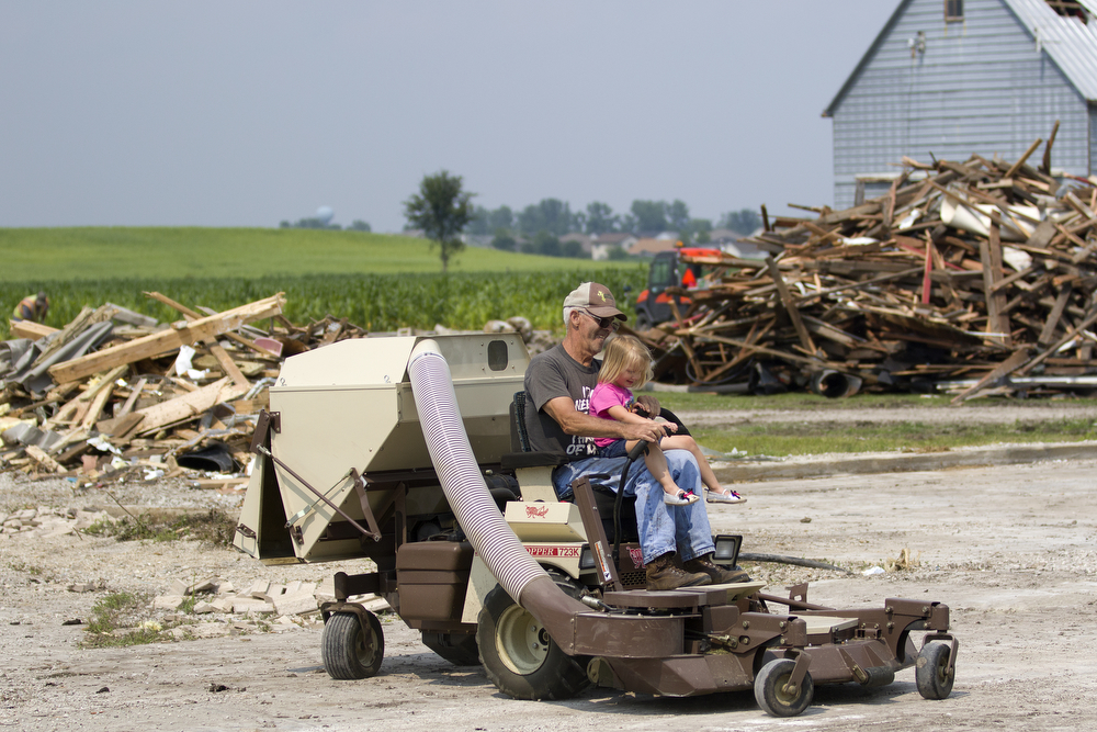 Emerlyn Kaluzny, 3, takes a ride with her uncle Wayne Morris as they help cleanup debris from the June 22 tornadoes on the family farm in Coal City, Ill. Tuesday, June 30, 2015. (Erin Hooley/Chicago Tribune)