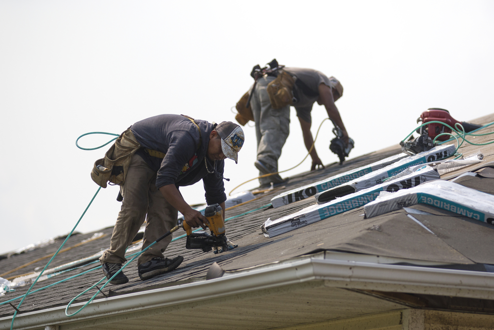 Roofers repair a home in the Coalfield subdivision that was damaged by the June 22 tornadoes in Coal City, Ill. Tuesday, June 30, 2015. (Erin Hooley/Chicago Tribune)