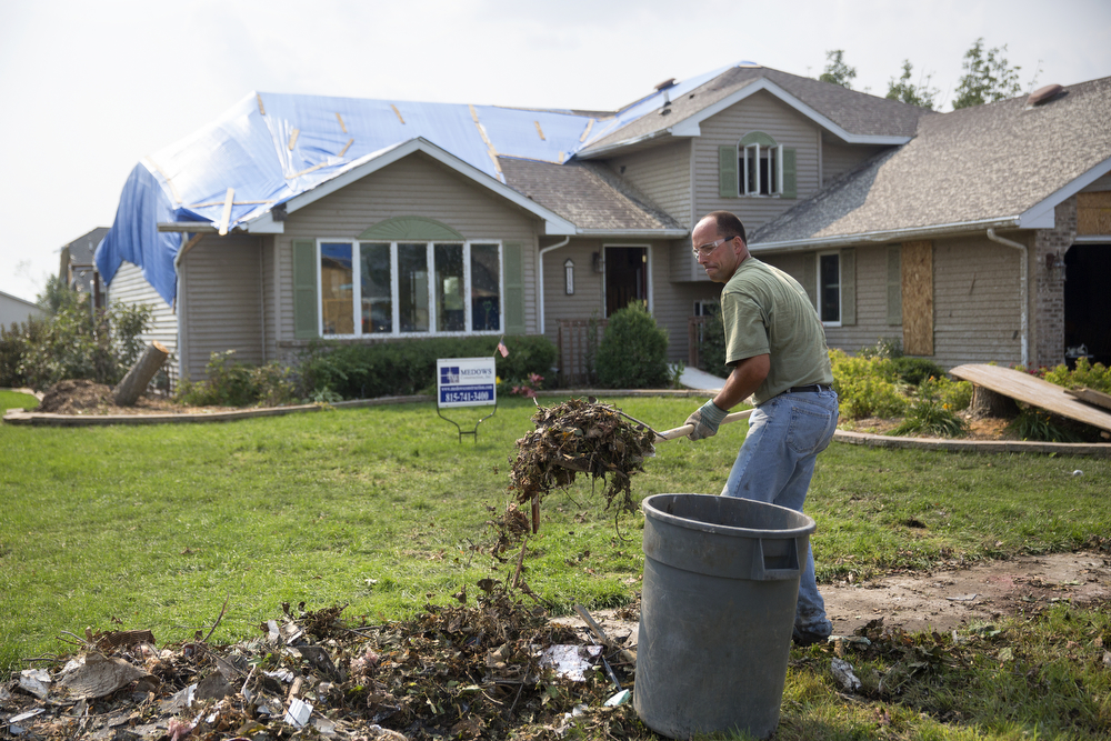 Grant Becker cleans up debris from the June 22 tornadoes outside his home in the Coalfield subdivision in Coal City, Ill. Tuesday, June 30, 2015. (Erin Hooley/Chicago Tribune)