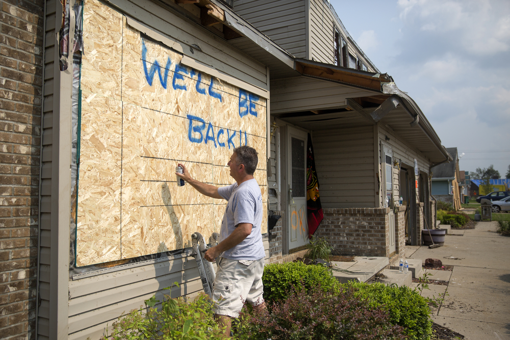 "Dan Greggain, whose Coalfield subdivision home was damaged by the June 22 tornadoes, spray paints ""We'll be back!! CC Strong"" on the outside of the building in Coal City, Ill. Tuesday, June 30, 2015. (Erin Hooley/Chicago Tribune)"