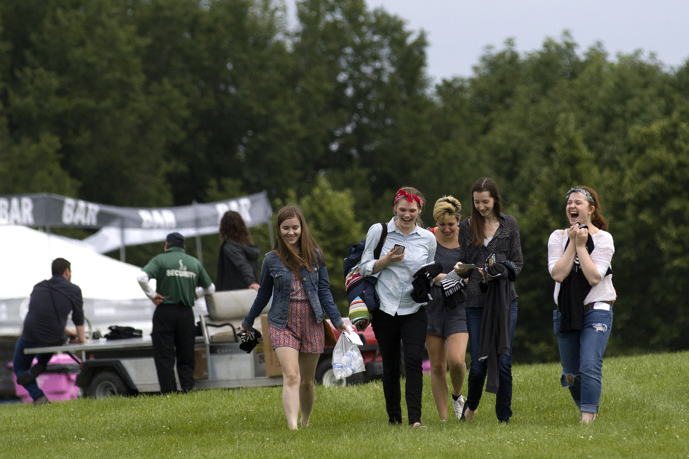 From left, Kaitlyn Crnich, Sarah Crawford, Allison Isom, Carey Dwyer and Rachel Fimbianti walk through Montrose Park after meeting members of the band Mumford & Sons Wednesday, June 17, 2015. The band was set to play a concert in the park Wednesday but the show has been postponed until Friday and the girls, who arrived early at the venue, said the band members came out to greet and personally apologize to fans for the postponement. (Erin Hooley/Chicago Tribune)
