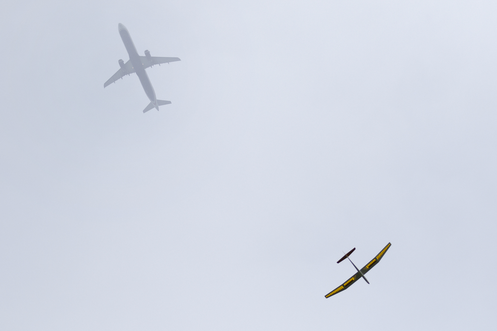 A toy glider flies overhead in Montrose Park as a real airplane heads for O'Hare International Airport in Chicago Wednesday, June 17, 2015.
