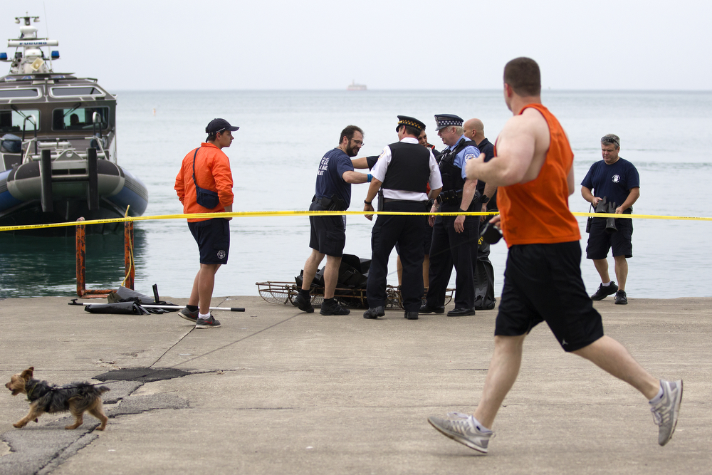 A runner and his dog pass Chicago Police Marine Unit officers and other police personnel as they prepare to remove a body that was found in Lake Michigan near Oak Street Beach in Chicago Monday, June 22, 2015. (Erin Hooley/Chicago Tribune)