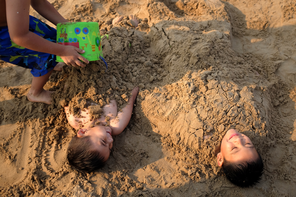 Santiago Cruz, left, 4, and Carlos Alcantar, 6, get buried in the sand at Montrose Beach in Chicago Saturday, July 4, 2015. (Erin Hooley/Chicago Tribune)