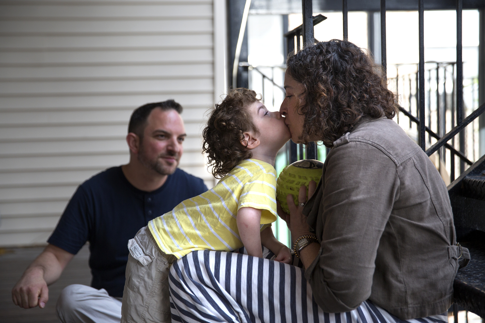 Aleck Persin, 3, gives his mother Lynn a kiss as he plays catch with her and his father Craig on the deck of their home in Logan Square Wednesday, July 22, 2015. (Erin Hooley/Chicago Tribune)