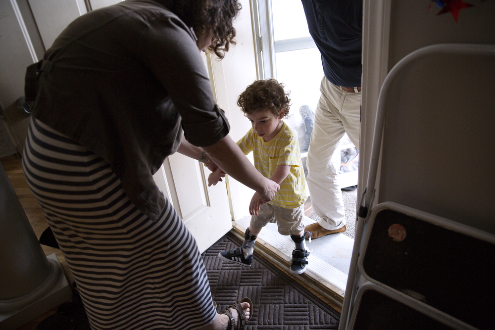 Lynn Persin, left, helps her son Aleck, 3, step over the back doorway into their home in Logan Square Wednesday, July 22, 2015. (Erin Hooley/Chicago Tribune)