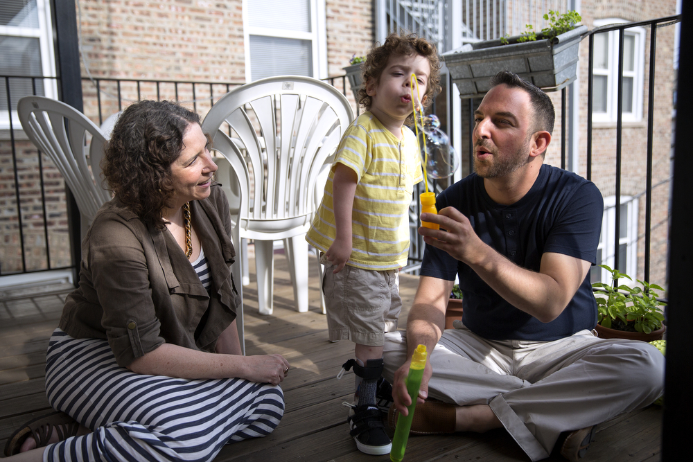 Aleck Persin, 3, blows bubbles with his mother Lynn and father Craig on the deck of their home in Logan Square Wednesday, July 22, 2015. (Erin Hooley/Chicago Tribune)