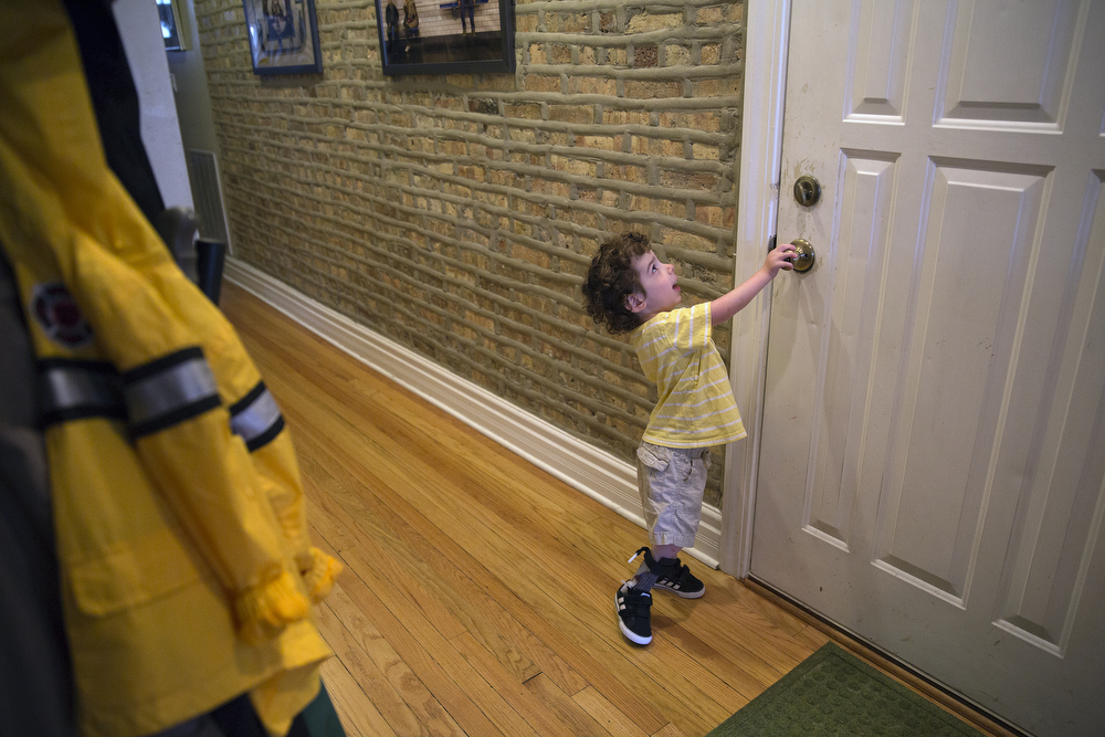 Aleck Persin, 3, shows how he can reach the doorknob of his front door as he prepares to go for a walk with his parents at his home in Logan Square Wednesday, July 22, 2015. (Erin Hooley/Chicago Tribune)