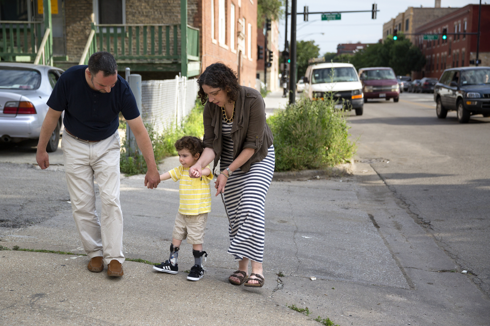 Aleck Persin, 3, gets help crossing an alley from his parents Lynn and Craig during a walk in their Logan Square neighborhood Wednesday, July 22, 2015. (Erin Hooley/Chicago Tribune)