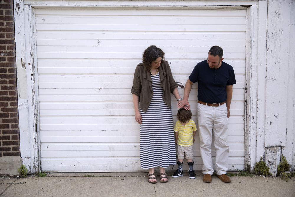 Lynn and Craig Persin stop to show their son Aleck, 3, how tall he is relative to a garage door in their Logan Square neighborhood Wednesday, July 22, 2015. (Erin Hooley/Chicago Tribune)