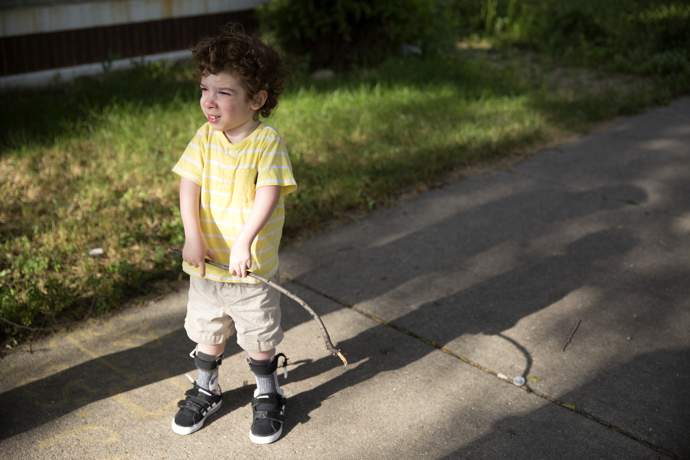 Aleck Persin, 3, stops for a moment during a walk with his parents Lynn and Craig in their Logan Square neighborhood Wednesday, July 22, 2015.  (Erin Hooley/Chicago Tribune)