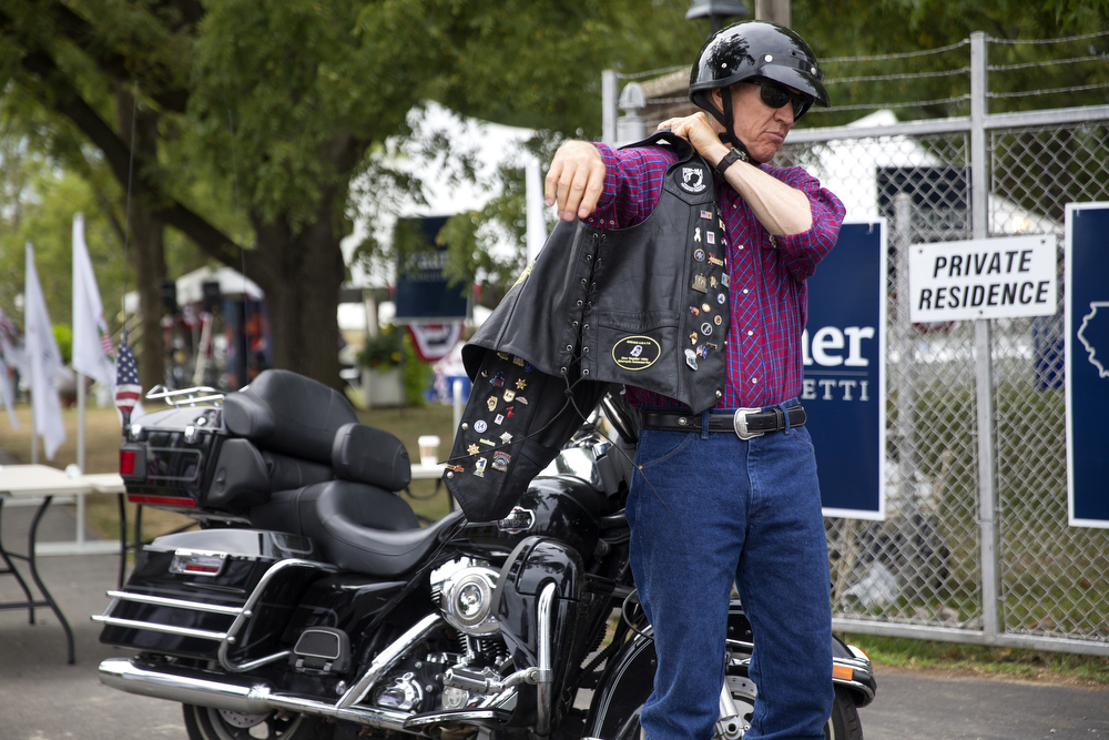 Gov. Bruce Rauner dons his leather vest as he departs Governor's Day on his Harley Davidson motorcycle Wednesday, August 19, 2015 at the Illinois State Fair in Springfield. (Erin Hooley/Chicago Tribune)