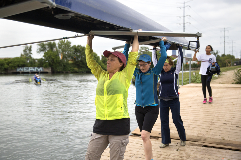 "Members of the Recovery on Water breast cancer survivors rowing crew, from left, Amee McMahon, Joan Neal, Nina Clark and Monica Bernardo carry a rowing shell to the dock on the South Fork of the Chicago River, also known as ""Bubbly Creek,"" August 26, 2015. The team practices on the river twice a week and launches from the area where the South Fork diverts from the South Branch, the historically polluted area that gets its nickname from the bubbling gases of decomposing waste in the water - leftovers disposed of in the river by meatpacking businesses in the Union Stock Yards area in the early 20th century. In the present day, Bubbly Creek takes on water and waste from oversaturated sewers during heavy rainstorms. The women of Recovery on Water are sure to use hand sanitizer directly after practice and change clothes and bathe immediately when they get home. (Erin Hooley/Chicago Tribune)"