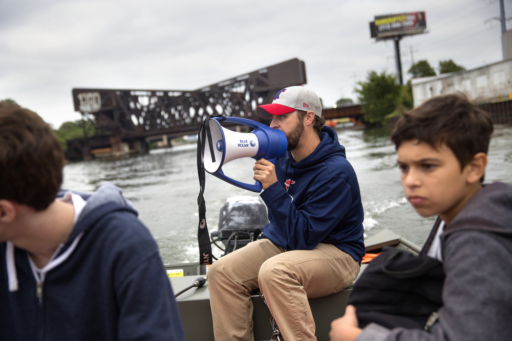 Devlin Murdock, operations and programs coordinator of Recovery on Water breast cancer survivors rowing group, uses a bullhorn to give directions during practice on the South Branch of the Chicago River August 26, 2015. (Erin Hooley/Chicago Tribune)