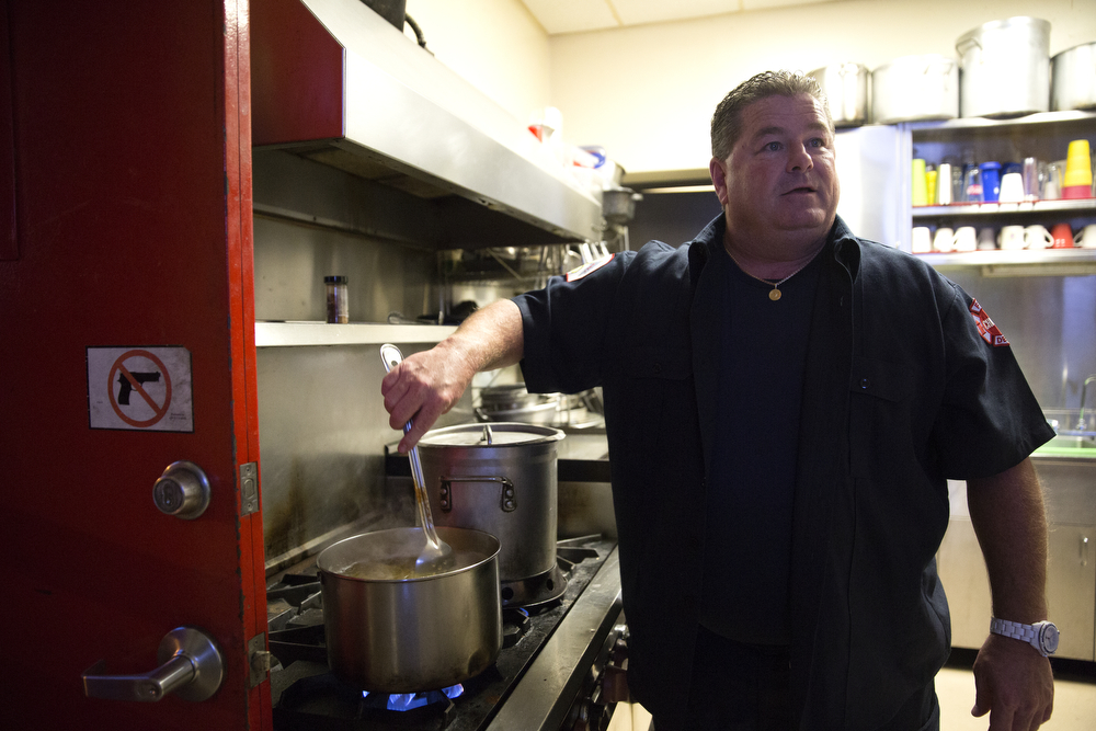 Firefighter Bob King cooks dinner at the Wrigleyville firehouse, home of Engine Co. 78 and Ambulance Co. 6, across from Wrigley Field, before game 3 of the National League Championship Series between the Chicago Cubs and the New York Mets Tuesday, Oct. 20, 2015. (Erin Hooley/Chicago Tribune)