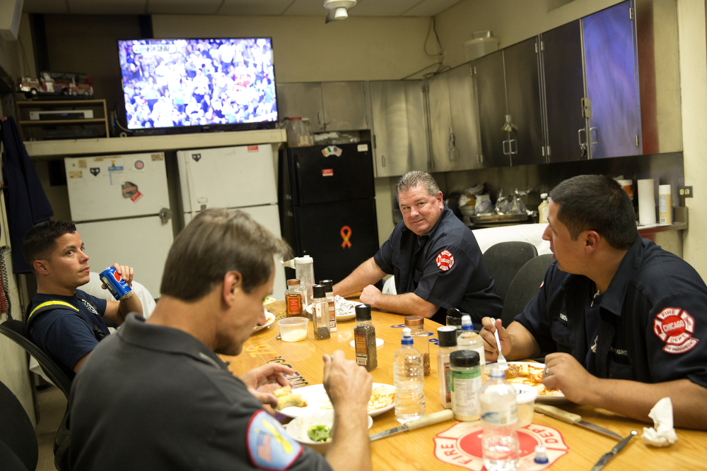 From left, firefighters Alan Negron, engineer Greg Piszkiewicz, Bob King and Sam Fakhoury eat dinner at the Wrigleyville firehouse, home of Engine Co. 78 and Ambulance Co. 6, across from Wrigley Field, during game 3 of the National League Championship Series between the Chicago Cubs and the New York Mets Tuesday, Oct. 20, 2015. (Erin Hooley/Chicago Tribune)