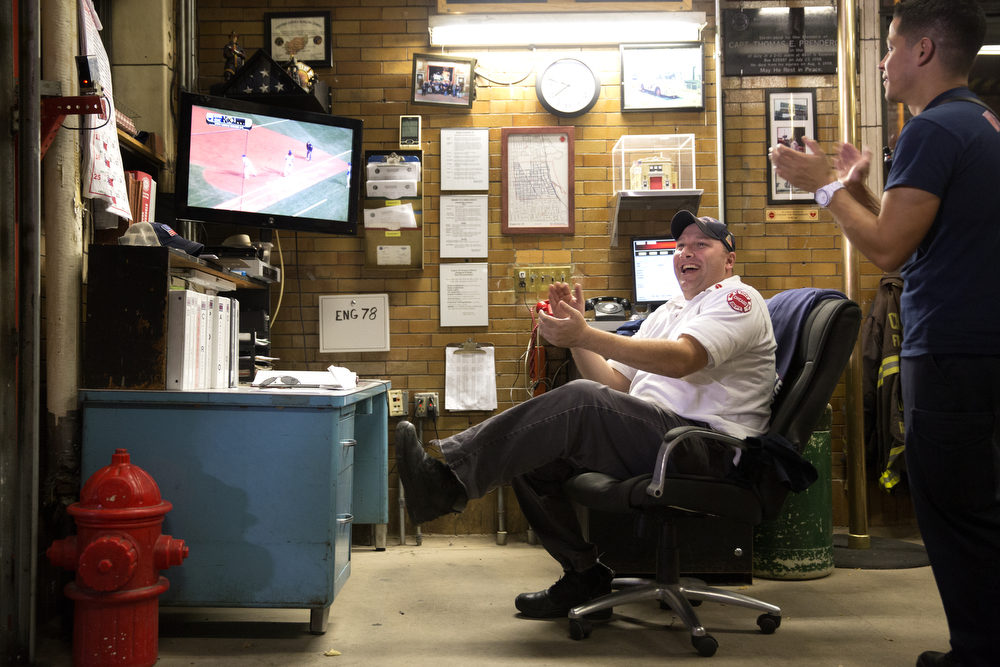 Lt. Daniel Reichenberger applauds a play as he watches the game with his fellow firefighters at the Wrigleyville firehouse, home of Engine Co. 78 and Ambulance Co. 6, across from Wrigley Field, during game 3 of the National League Championship Series between the Chicago Cubs and the New York Mets Tuesday, Oct. 20, 2015. (Erin Hooley/Chicago Tribune)