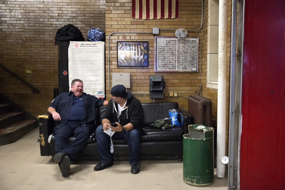 Firefighter Bob King, left, chats with a baseball fan at the Wrigleyville firehouse, home of Engine Co. 78 and Ambulance Co. 6, across from Wrigley Field, before game 3 of the National League Championship Series between the Chicago Cubs and the New York Mets Tuesday, Oct. 20, 2015. (Erin Hooley/Chicago Tribune)
