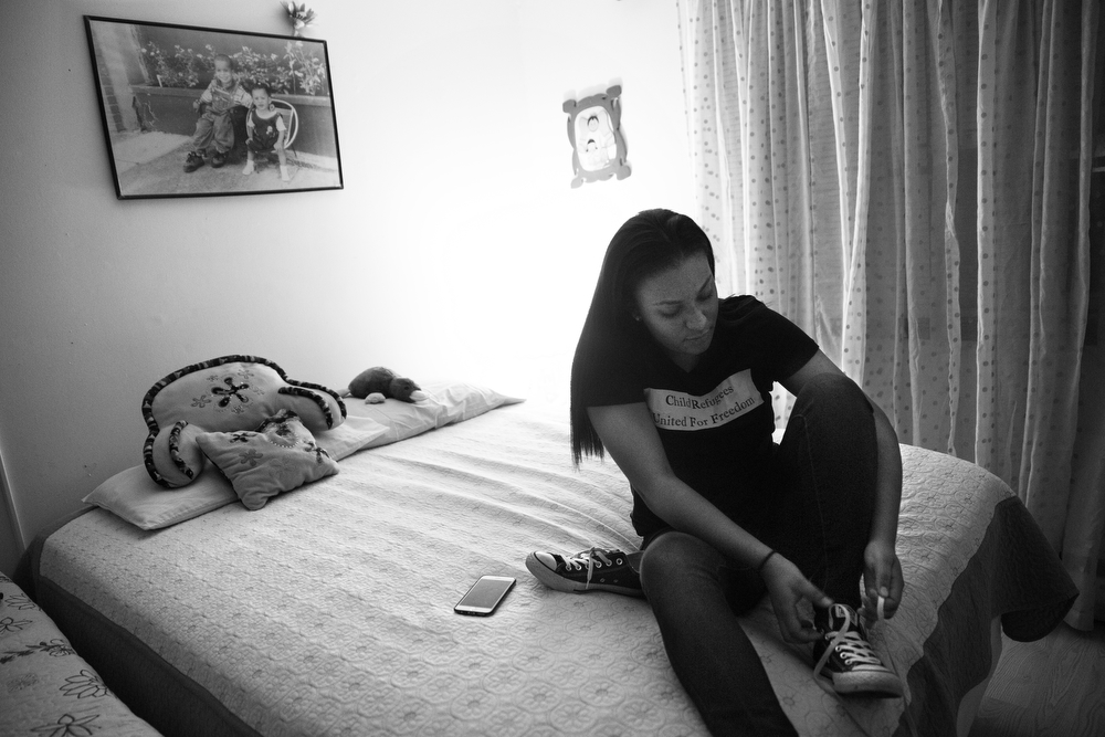 15-year-old Maryori Urbina-Contreras puts on her shoes in her bedroom as she prepares for the journey from her home in Waukegan to an immigration hearing at Chicago Immigration Court Wednesday, Oct. 28, 2015. Fleeing violence in her home country of Honduras, Maryori travelled alone for several weeks in 2014 before reuniting with her mother, who has been in the United States since 2001. Her ongoing immigration case will eventually determine if she is allowed to stay in the U.S. or be forced to return to Honduras. (Erin Hooley/Chicago Tribune)