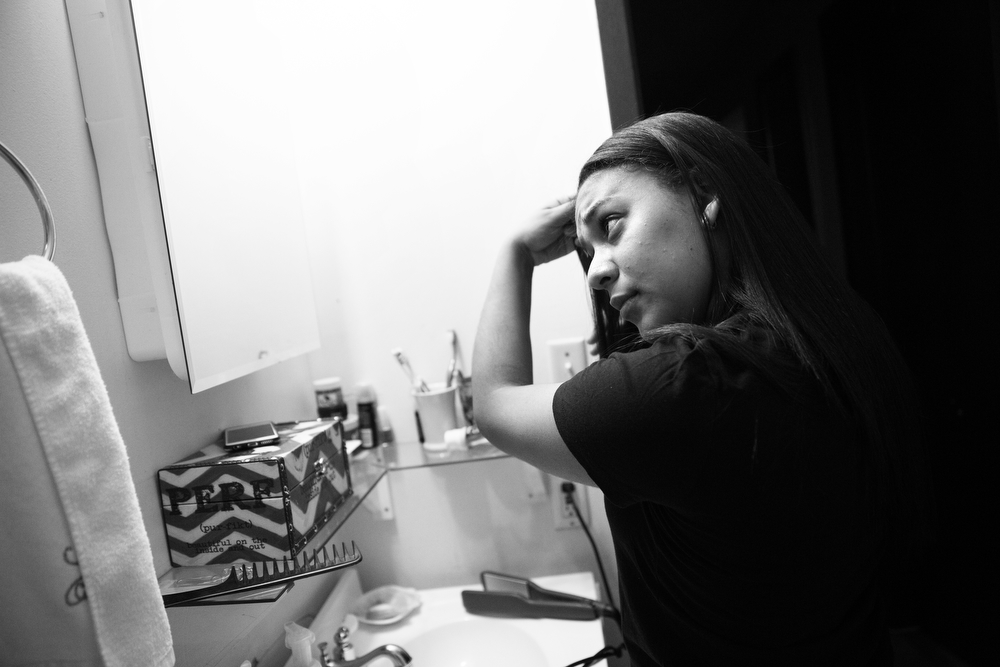 Maryori looks into a bathroom mirror as she brushes her hair in preparation for her immigration hearing at Chicago Immigration Court. She currently shares a room with her two younger siblings, both born in the United States, in the apartment with her mother and stepfather. (Erin Hooley/Chicago Tribune)