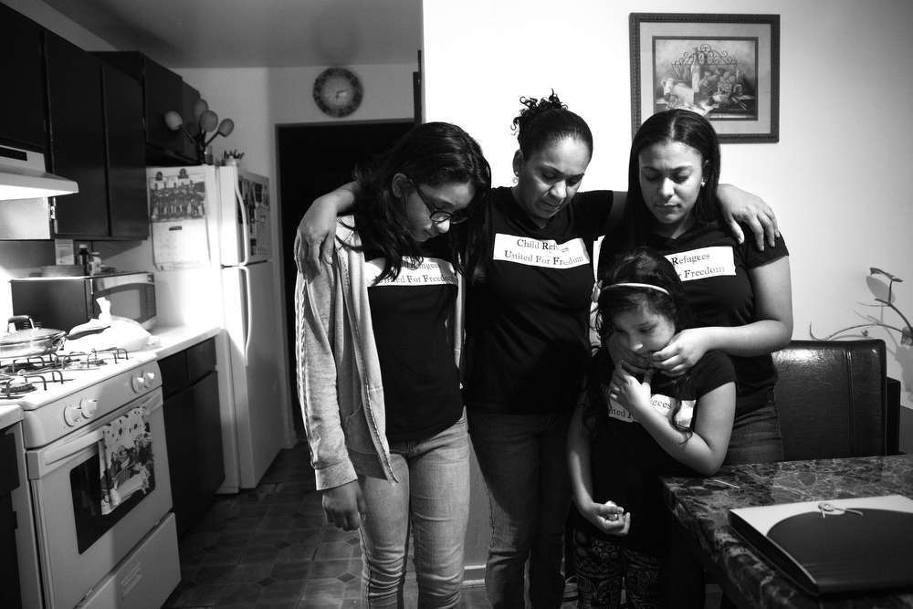 "Mother Tania Contreras Guerrero, center, prays with Maryori and her younger daughters Diana Ruiz, left, 11, and Valeria Ruiz, bottom, 6, as they prepare for the journey to Chicago for Maryori's immigration hearing. Tania was worried her daughter might be deported. Quietly, she said, ""Don't take her from me, Lord. You know how much I've struggled. I don't want to lose her, to lose my heart."" (Erin Hooley/Chicago Tribune)"