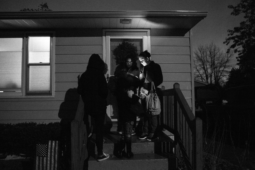 The family waits in the dark outside the home of Julie Contreras (no relation), a volunteer with the League of United Latin American Citizens of Lake County, in Waukegan. Julie is an advocate for several Honduran children who crossed the border alone and helped Maryori find a lawyer for her case and previously drove the family to other court hearings. (Erin Hooley/Chicago Tribune)