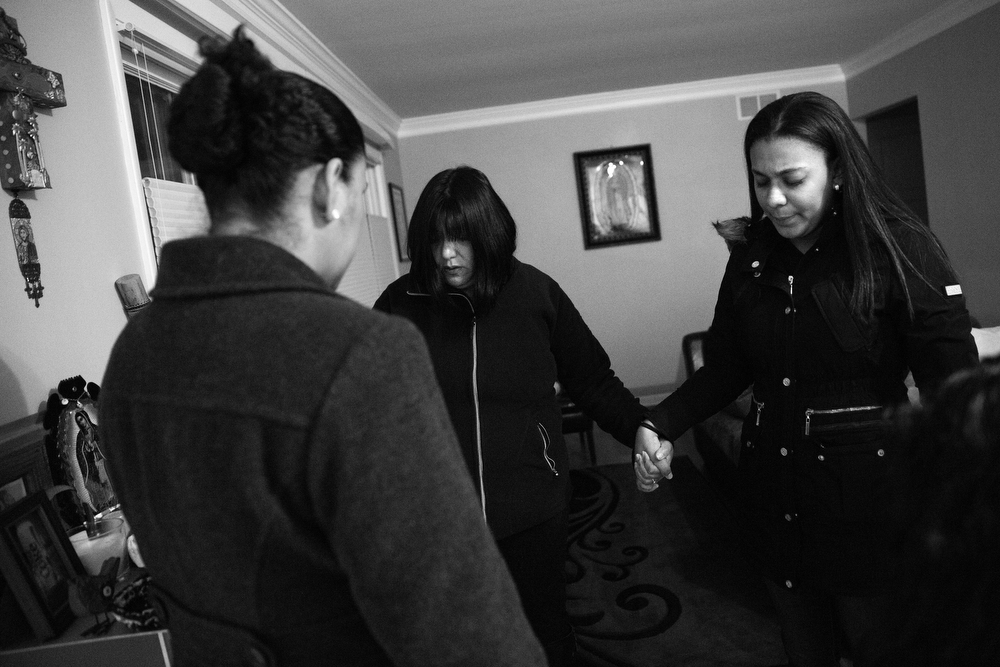 Maryori, right, holds hands with her family as they again pray at the home of Julie Contreras in Waukegan before driving with her to court in Chicago. (Erin Hooley/Chicago Tribune)
