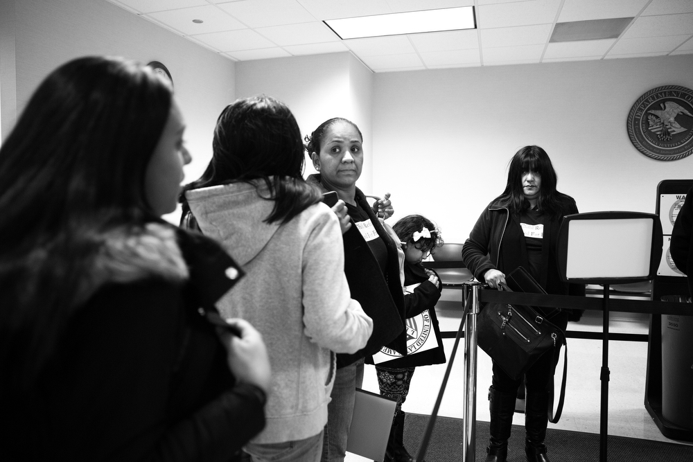 The family waits in line to go through security at immigration court, where photography of any kind is not permitted. (Erin Hooley/Chicago Tribune)