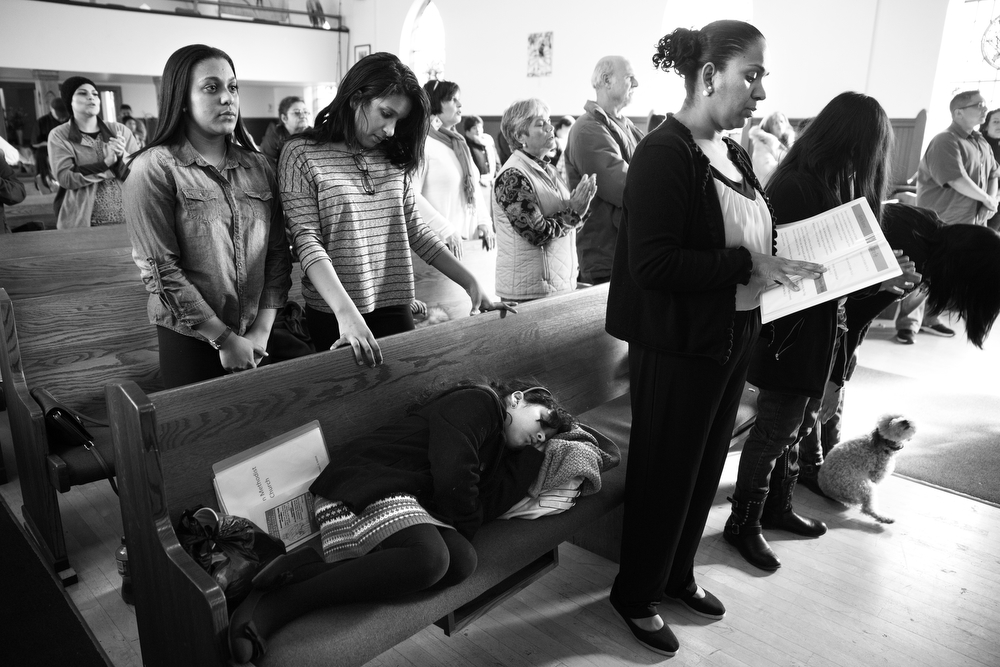 Maryori, left, Diana, center, and mother, Tania, right, stand during mass as Valeria sleeps, at Lincoln United Methodist Church Sunday, Nov. 8, 2015 in Chicago. The family is able to return to normal life for the time being. (Erin Hooley/Chicago Tribune)