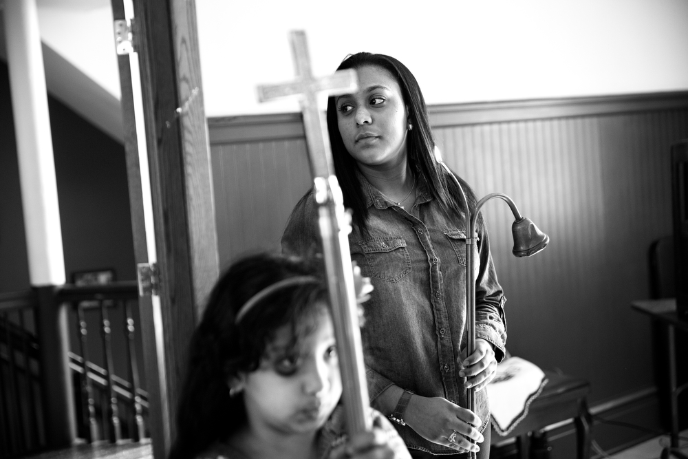 Maryori Urbina-Contreras holds a candle lighter and extinguisher as she acts as an acolyte during mass with her family at Lincoln United Methodist Church Sunday, Nov. 8, 2015 in Chicago. Her ongoing immigration case will eventually determine if she is allowed to stay in the U.S. or be forced to return to Honduras. (Erin Hooley/Chicago Tribune)