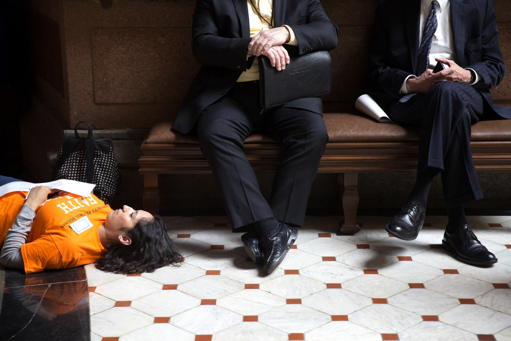 "Maria Torres lies on the ground with other members of The Community Renewal Society as they stage a ""die-in"" as part of their ""Faith in Action"" campaign at the Illinois State Capitol Tuesday, May 12, 2015 in Springfield. The faith-based organization involves members from many different churches and works ""to eliminate race and class barriers."" (Erin Hooley/Chicago Tribune)"