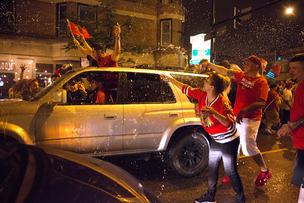 People in a crowd spray a passing vehicle with beer as fans celebrate the Chicago Blackhawks' Stanley Cup win over the Tampa Bay Lightning Monday, June 15, 2015 in Wrigleyville. This is the third time the Blachkawks have won the Cup in the last six seasons. (Erin Hooley/Chicago Tribune)