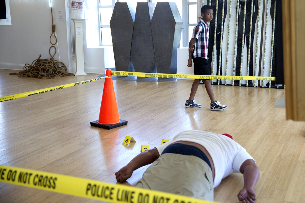 "A young visitor passes the ""Angelitos Negros"" art installation depicting a life-size replica of the body of Michael Brown and the crime scene where he was shot by police officer Darren Wilson in Ferguson, Mo. last year, at the ""Confronting Truths: Wake Up!"" exhibition featuring works by New Orleans artist Ti-Rock Moore at Gallery Guichard Fine Art Gallery Sunday, July 12, 2015 in Bronzeville. Moore's artist statement about this piece reads: ""Angelitos Negros is a reflection on Michael Brown's brutal murder by the Ferguson, Missouri police last year. The installation introduces a silicone replica of Brown's dead body with Eartha Kitt's controversial 1950s song 'Angelitos Negros' or 'Little Black Angels' playing in the backdrop, calling attention to the racial injustices that existed then and remain devastatingly relevant today."" (Erin Hooley/Chicago Tribune)"