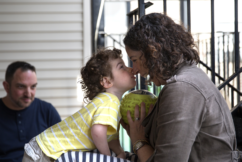 Aleck Persin, 3, gives his mother Lynn a kiss as he plays catch with her and his father Craig on the deck of their home in Logan Square Wednesday, July 22, 2015 in Chicago. Aleck was born with arthrogryposis, a condition caused by multiple joint contractures and characterized by muscular fibrosis and inhibited movement of the joints. (Erin Hooley/Chicago Tribune)