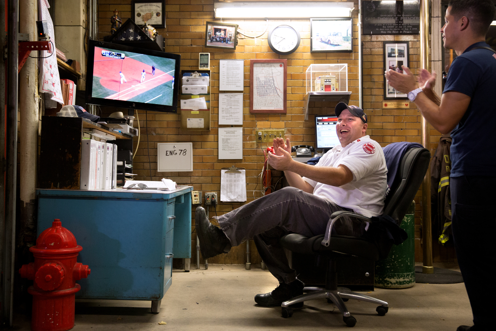 Lt. Daniel Reichenberger applauds with laughter during a play as he watches game 3 of the National League Championship Series between the Chicago Cubs and the New York Mets Tuesday, Oct. 20, 2015 at the Wrigleyville firehouse, home of Engine Co. 78 and Ambulance Co. 6, across from Wrigley Field in Chicago. Lt. Reichenberger explained how the roar of fans across the street precedes what's happening on the television by an eleven-second broadcast delay.  (Erin Hooley/Chicago Tribune)