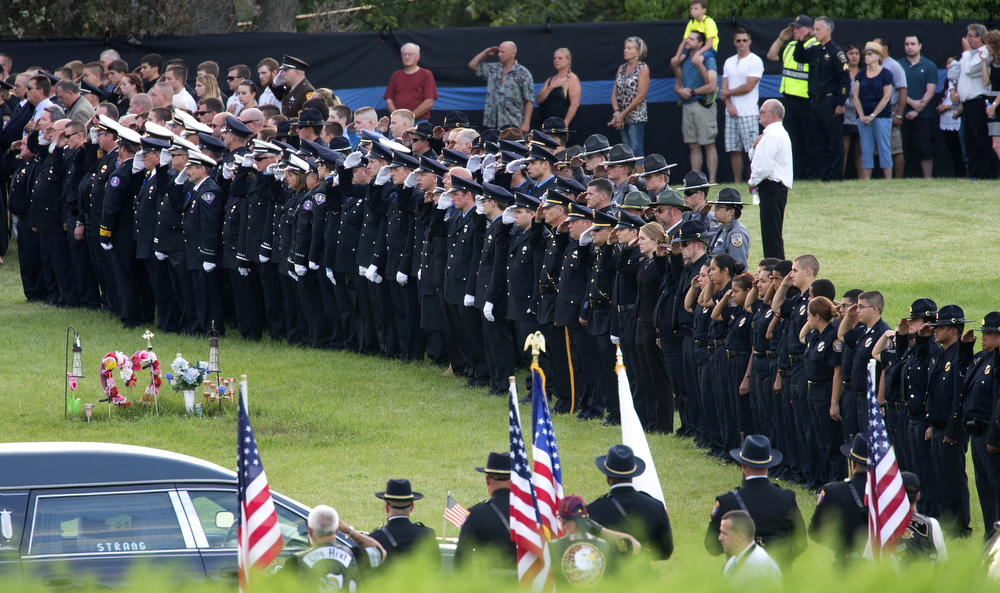 Fellow officers stand in salute of Fox Lake police Lt. Charles Joseph Gliniewicz during his funeral at Hillside East Cemetery Monday, Sept. 7, 2015 in Antioch, Ill. Officers responded to a radio call from Lt. Gliniewicz on September 1 that he was chasing three suspicious men into a swampy area and later found him fatally shot. After an extensive manhunt involving dogs and helicopters, the suspects were never caught and an investigation into the incident revealed two months later that Lt. Gliniewicz's death was a suicide. It also revealed he had been embezzling from the village's police youth program for seven years. (Erin Hooley/Chicago Tribune)