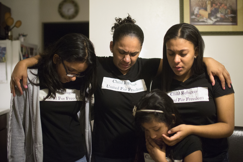 Tania Contreras Guerrero, center, prays with her daughters Diana Ruiz, left, 11, Maryori Urbina Contreras, right, 15, and Valeria Ruiz, bottom, 6, as they prepare for the journey from their home in Waukegan to an immigration hearing at Chicago Immigration Court Wednesday, Oct. 28, 2015. Fleeing violence in her home country of Honduras, Maryori travelled alone for several weeks in 2014 before reuniting with her mother, who has been in the United States since 2001. Her ongoing immigration case will eventually determine if she is allowed to stay in the U.S. or be forced to return to Honduras. Tania was worried her daughter might be deported. (Erin Hooley/Chicago Tribune)
