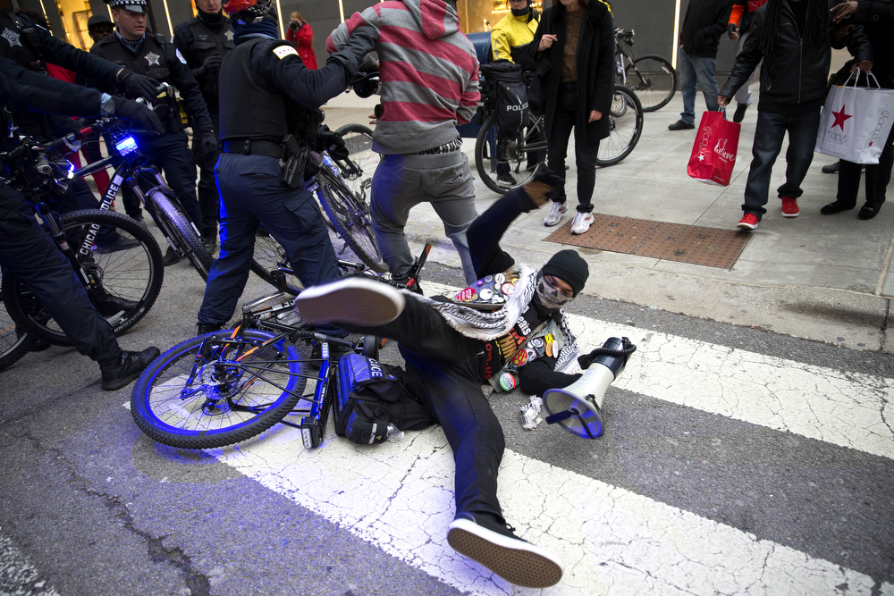 "Protesters and police officers clash during a ""Black Christmas"" protest along Michigan Avenue Thursday, Dec. 24, 2015 in Chicago. Protesters blocked streets and stores along the Magic Mile, calling for the resignation of Mayor Rahm Emanuel after the release of a video showing the death of Laquan McDonald, who was shot 16 times and killed by Chicago police Officer Jason Van Dyke last year. (Erin Hooley/Chicago Tribune)"