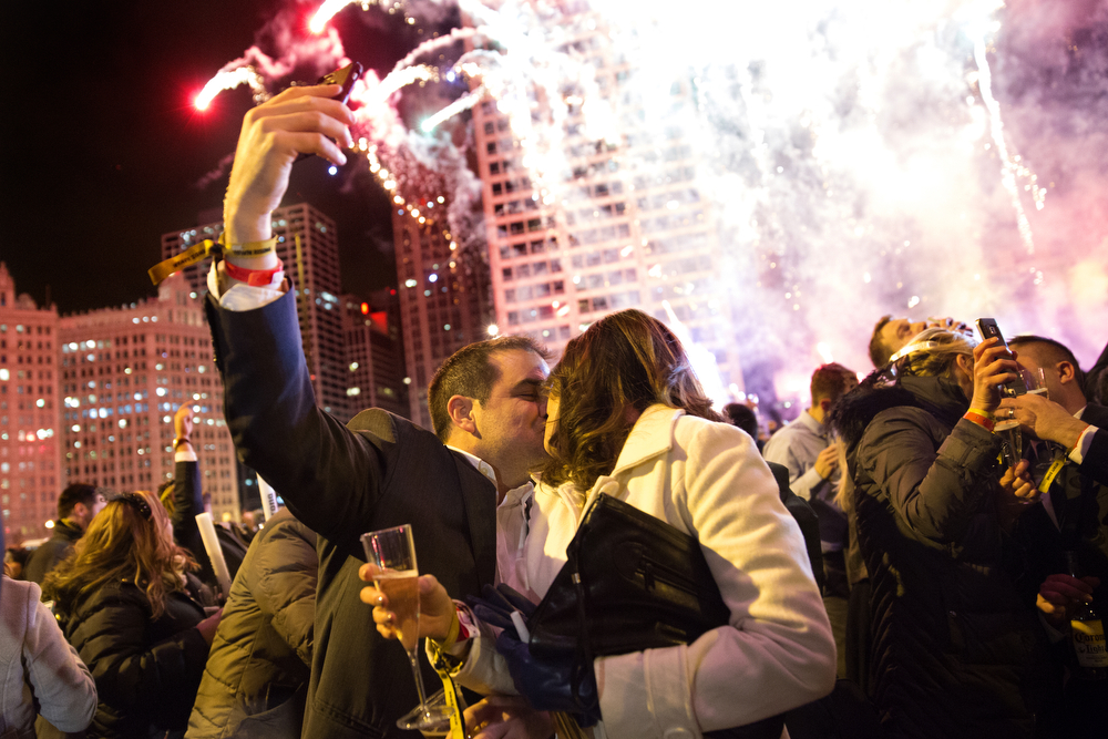 A couple shares a kiss as fireworks go off over the Chicago River during the Chi-Town Rising New Year's Eve event shortly after midnight Friday, Jan. 1, 2016 in downtown Chicago. (Erin Hooley/Chicago Tribune)