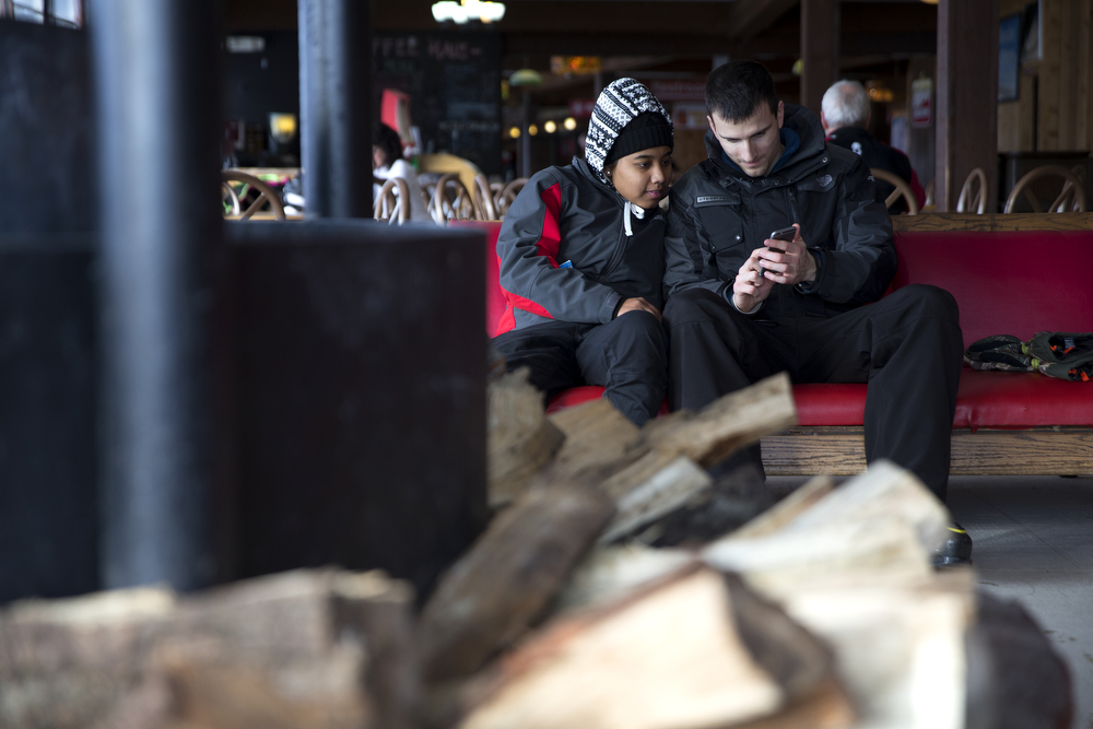 Sharise Campbell, left, and Nemanja Uzelac, both of Chicago, look at a phone at they sit by the fire at Wilmot Mountain Ski Resort Wednesday, Jan. 20, 2016, in Wilmot, Wis. The Colorado-based company Vail Resorts recently purchased Wilmot. (Erin Hooley/Chicago Tribune)
