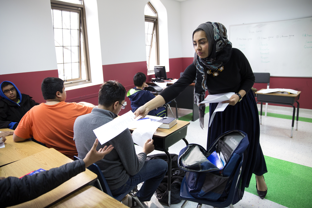 Saarah Bhaiji, 16, hands tests back to students as she helps out Dr. Sabah Khan in her Islamic theology class at the Muslim Education Center Sunday, Jan. 31, 2016, in Morton Grove, Ill. Bhaiji teaches and occasionally helps out at the center on Sundays and attends Glenbrook South High School as a junior during the week, where she said her experience as a Muslim has been mostly positive. (Erin Hooley/Chicago Tribune)