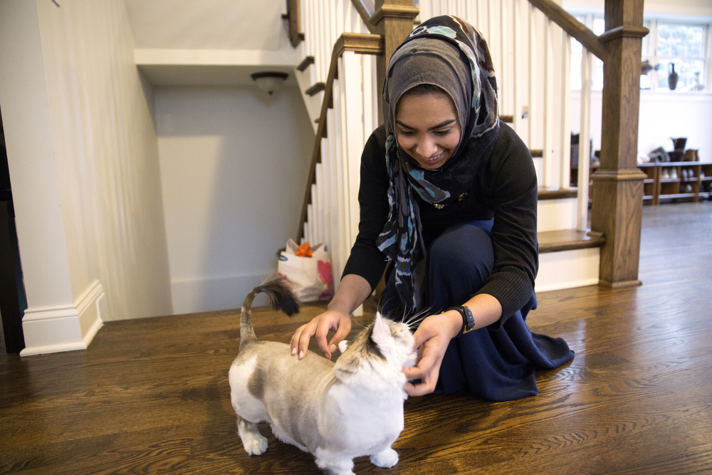 Saarah Bhaiji, 16, greets her cat Tokyo at her home Sunday, Jan. 31, 2016, in Glenview, Ill. Bhaiji teaches at the Muslim Education Center in Morton Grove on Sundays and attends Glenbrook South High School as a junior during the week, where she said her experience as a Muslim has been mostly positive. (Erin Hooley/Chicago Tribune)