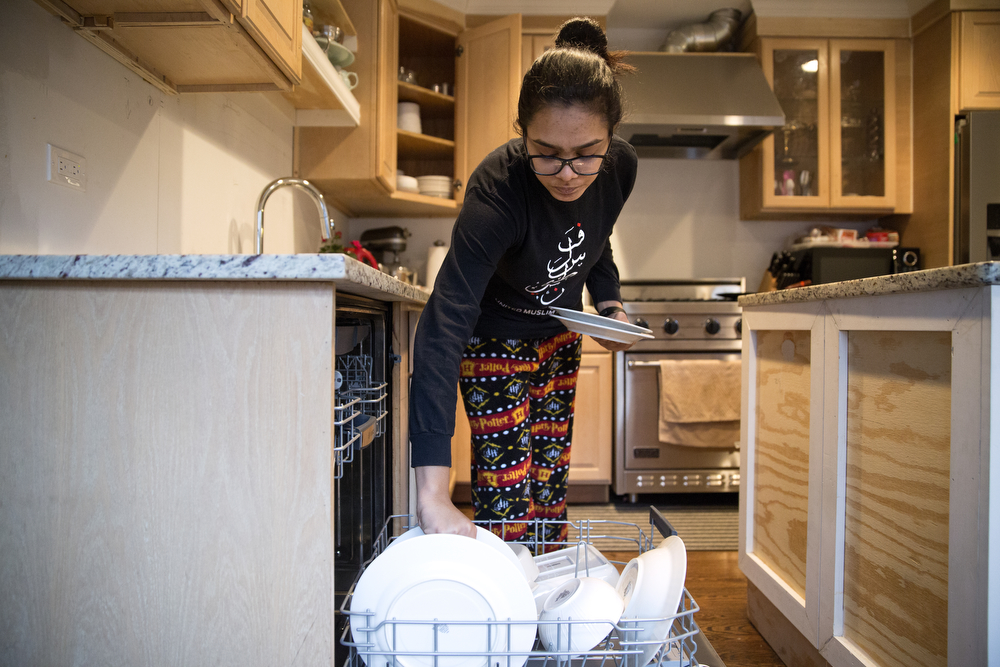 Aasiyah Bhaiji, 13, puts dishes away at her home Sunday, Jan. 31, 2016, in Glenview, Ill. Bhaiji, whose family is Muslim, wears a headscarf to Sunday school at the Muslim Education Center but takes it off when she gets home and doesn't wear one in public. (Erin Hooley/Chicago Tribune)
