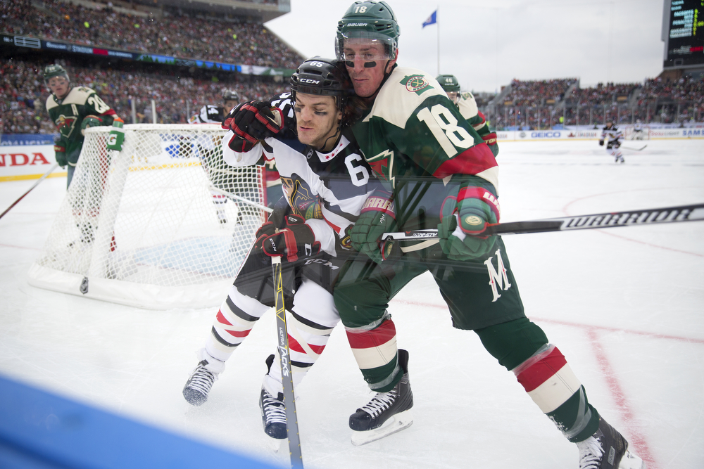 Chicago Blackhawks center Andrew Shaw (65), left, and Minnesota Wild center Ryan Carter (18) scuffle behind the Wild's net during the first period of the Chicago Blackhawks versus Minnesota Wild 2016 NHL Stadium Series outdoor game at TCF Bank Stadium on the University of Minnesota Campus Sunday, Feb. 21, 2016, in Minneapolis. (Erin Hooley/Chicago Tribune)