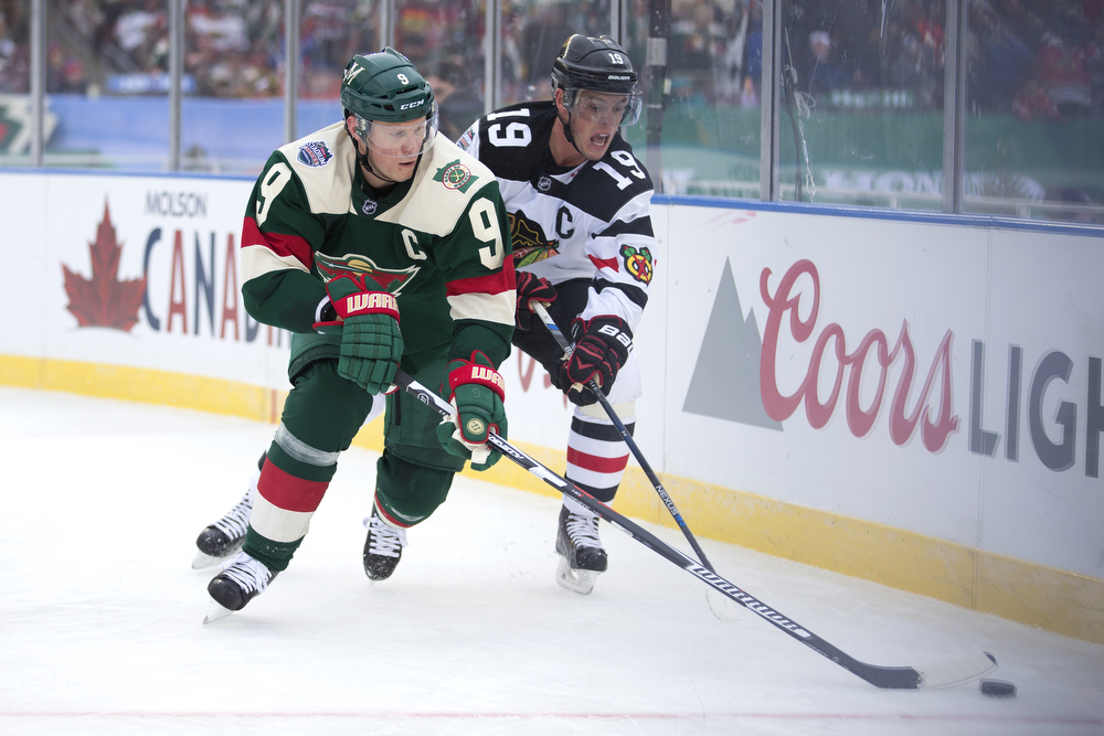 Minnesota Wild center Mikko Koivu (9), left, and Chicago Blackhawks center Jonathan Toews (19) chase down the puck during the second period of the Chicago Blackhawks versus Minnesota Wild 2016 NHL Stadium Series outdoor game at TCF Bank Stadium on the University of Minnesota Campus Sunday, Feb. 21, 2016, in Minneapolis. The Wild beat the Blackhawks 6-1. (Erin Hooley/Chicago Tribune)